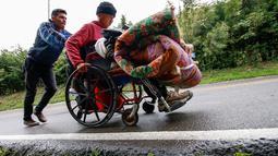 Migran Venezuela, Jefferson Alexis mendorong kursi roda ayahnya, Jose Agustin Lopez di Norte de Santander Department, Kolombia, 15 September 2018. Sang ayah mengalami cacat dan terkena luka infeksi daerah anus dan rektum. (AFP/SCHNEYDER MENDOZA)