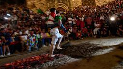 Seorang pria membawa anak lelaki di punggungnya sambil berjalan di atas bara api selama malam San Juan di San Pedro Manrique, Spanyol Utara, Minggu (24/6). Tradisi kuno Spanyol ini diperingati untuk menyambut musim panas. (AP Photo/Alvaro Barrientos)