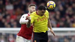 Bek Arsenal, Shkodran Mustafi, duel udara dengan striker Watford, Troy Deeney, pada laga Preimer League di Stadion Emirates, Minggu (11/3/2018). Arsenal menang 3-0 atas Watford. (AP/Matt Dunham)