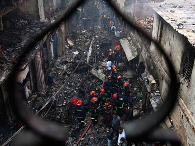 Petugas pemadam kebakaran terlihat di lokasi kebakaran di Dhaka (21/2). Setidaknya 69 orang tewas dalam kebakaran besar yang melanda gedung apartemen yang juga digunakan sebagai gudang bahan kimia di Bangladesh tersebut. (AFP Photo/Munir Uz Zaman)