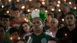 Seorang fans Chapecoense dengan penutup kepala berbulu memperingati satu tahun kecelakaan pesawat Lamia 2933 di Arena Conda stadium, Chapeco, Santa Catarina, Brasil, (28/11/2017). Sekitar 19 pemain Chapecoense meninggal. (AFP/Nelson Meida)