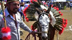 Seekor keledai dihias saat mengikuti National Donkey Fair di Otumba, Meksiko (1/5). Acara tahunan ini diikuti sekitar 7.000 orang. Dalam acara ini peserta membawa keledainya yang dihias dengan berbagai macam atribut. (AFP Photo/Pedro Pardo)