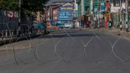 Kawat berduri dipasang untuk memblokir jalan yang sepi di Srinagar, Kashmir yang dikuasai India, Rabu (5/8/2020). Pasukan dan barikade kawat berduri dikerahkan oleh India dalam upaya menahan serangan pada peringatan setahun pelepasan status otonomi khusus wilayah tersebut. (AP Photo/ Dar Yasin)