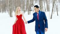Kemesraan Panji dan Varsha saat liburan ke Jepang. Terlihat gagah dengan balutan jas biru dan istrinya elegan dengan balutan gaun merah yang menyala diantara salju putih (Liputan6.com/IG/@varshaadhikumoro)