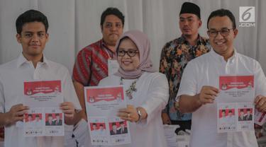 Gubernur DKI Anies Baswedan bersama istri Fery Farhati Ganis dan anaknya menunjukkan surat suara sebelum mencoblosnya di TPS 60, Cilandak, Jakarta Selatan, Rabu (17/4). Adapun pencoblosan Pemilu 2019 dilakukan serentak hari ini pada pukul 07.00-13.00 waktu setempat. (Liputan6.com/Faizal Fanani)