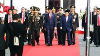 Presiden Jokowi didampingi Wapres Jusuf Kalla dan Kapolri Jenderal Pol Tito Karnavian saat menghadiri peringatan HUT ke-71 Bhayangkara di Monas, Jakarta, Senin (10/7). Jokowi menjadi instruktur upacara dalam acara tersebut. (Liputan6.com/Angga Yuniar)