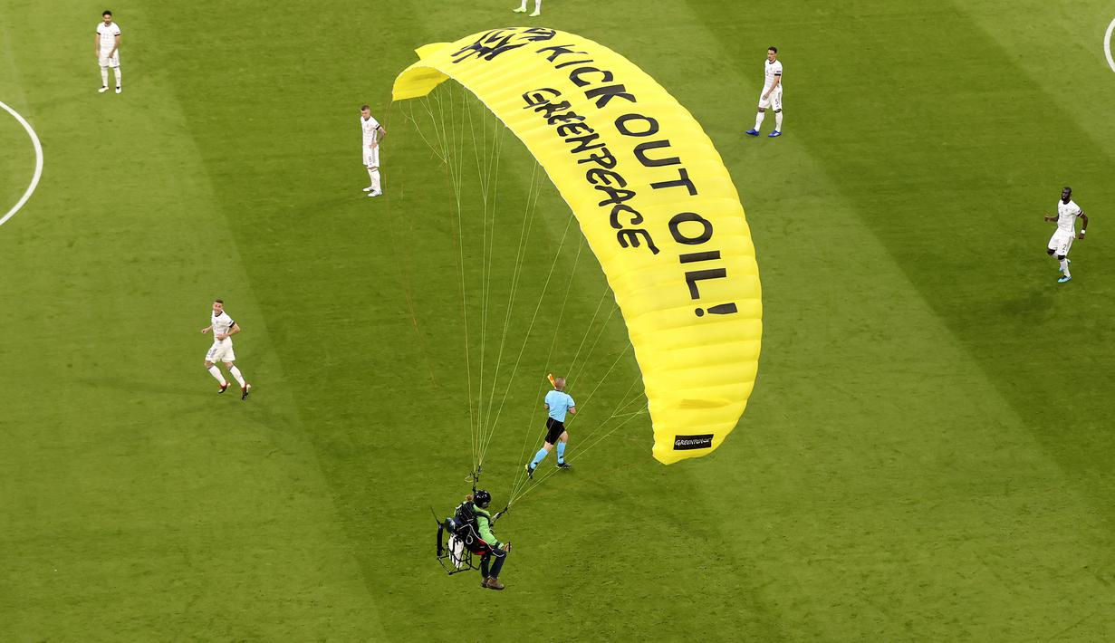 "Para pemain melihat paraglider Greenpeace mendarat di stadion sebelum pertandingan Grup F Euro 2020 antara Prancis dan Jerman di Allianz Arena, Munich, Jerman, Selasa (15/6/2021). Pada parasut kuning sang aktivis tertulis ""Kick Out Oil! Greenpeace"". (AP Photo/ctivist Alexander Hassenstein, Pool)"