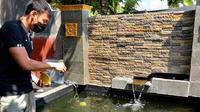 Kiper PSS Sleman, Ega Rizky dengan kesibukan barunya memelihara ikan koi di rumahnya. (Dok PSS)