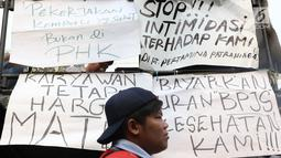 Sejumlah tulisan ditempelkan saat unjuk rasa di depan gedung Kementerian Ketenagakerjaan, Jakarta, Kamis (6/7). Massa menuntut agar seluruh sopir tangki BBM Pertamina Patra Niaga dan Elnusa Petrofin karyawan tetap. (Liputan6.com/Immanuel Antonius)