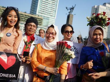 Relawan memegang bunga mawar untuk dibagikan ke pengunjung car free day di kawasan Bundaran HI, Jakarta, Minggu (30/6/2019).  Aksi 1000 bunga mawar itu sebagai bentuk rasa syukur atas kemenangan pasangan Jokowi-Ma'ruf Amin di Pilpres 2019. (Liputan6.com/Immanuel Antonius)