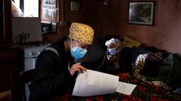 Petugas medis memeriksa dokumen usai melakukan vaksinasi virus corona COVID-19 Moderna untuk penduduk berusia di atas 80 tahun di Elva, Lembah Maira, dekat Cuneo, Italia barat laut, 17 April 2021. (MARCO BERTORELLO/AFP)