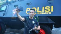 Beny Wahyudi selfie di depan rantis sebelum bertolak menuju Stadion Gelora Delta, Sidoarjo, untuk melawan Bhayangkara FC, Sabtu (19/9/2016). (Bola.com/Iwan Setiawan)