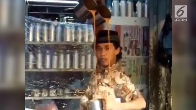 Aksi seorang pria mebuat teh tarik sambil menari seperti balerina.