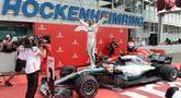 Pembalap Mercedes, Lewis Hamilton berselebrasi setelah berhasil finish pertama pada balapan F1 GP Jerman di Sirkuit Hockenheim, Minggu (22/7). Kemenangan ini diraih secara dramatis karena Hamilton mengawali balapan dari urutan ke-14. (AP/Jens Meyer)