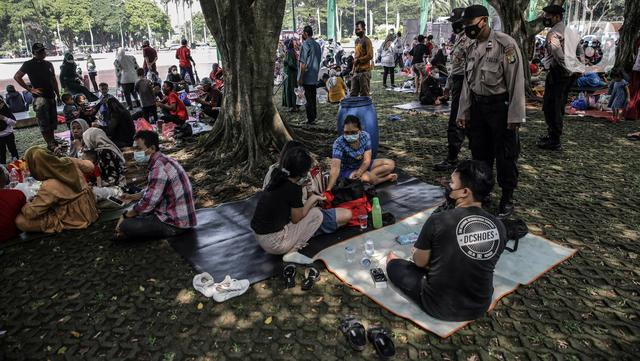 Polisi melakukan sosialisasi protokol kesehatan kepada para pengunjung yang berwisata di Taman Mini Indonesia Indah (TMII), Jakarta, Sabtu (15/5/2021). Banyak warga memilih berwisata ke TMII untuk menghabiskan waktu libur Lebaran. (Liputan6.com/Faizal Fanani)