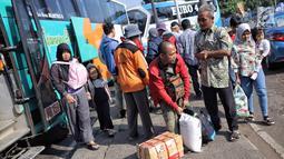 Suasana saat penumpang turun dari bus Antar Kota Antar Provinsi (AKAP) di Terminal Kampung Rambutan, Jakarta, Selasa (19/6). Jumlah kedatangan penummpang diperkiran terus bertambah hingga malam nanti. (Liputan6.com/Faizal Fanani)