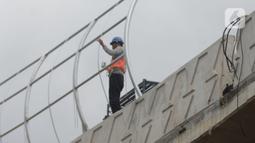 Pekerja beraktivitas di proyek pembangunan jalan layang (flyover) Cakung, Jakarta, Kamis (28/1/2021). Pembangunan jalan  layang dengan panjang 760 meter dan lebar 18 meter ini bertujuan sebagai pengganti pelintasan sebidang kereta api. (merdeka.com/Imam Buhori)