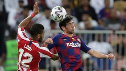 Pemain Atletico Madrid Renan Lodi berebut bola dengan bek Barcelona Sergi Roberto, pada laga semifinal Piala Super Spanyol di King Abdullah Sports City, Jeddah, Kamis (9/1/2020). Barcelona harus menjalani pertandingan yang dramatis saat kalah 2-3 dari Atletico Madrid. (AP/Hassan Ammar)