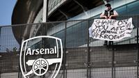 Seorang penggemar Arsenal membentangkan spanduk anti Liga Super Eropa di luar Stadion Emirates, London, Senin (19/4/2021). (Foto: AFP/Tolga Akmen)