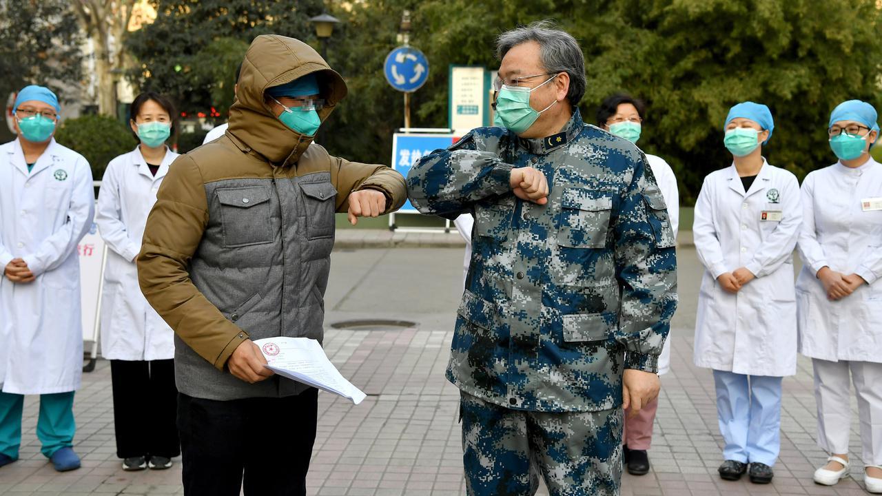 Pasien yang dinyatakan sembuh dari virus corona beradu siku dengan petugas medis di Rumah Sakit Tangdu Universitas Kedokteran Militer Angkatan Udara Xi'an, Provinsi Shaanxi, China, Selasa (4/2/2020). Ini adalah pasien pertama yang dinyatakan sembuh dari virus corona di Shaanxi. (Xinhua/Liu Xiao)