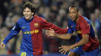Bintang Barcelona, Lionel Messi, bersama rekannya Thierry Henry merayakan gol yang dicetaknya ke gawang Lyon pada babak grup Liga Champions di Stadion Camp Nou, Barcelona, Rabu (11/3/2009). (AFP/Philippe Desmazes)