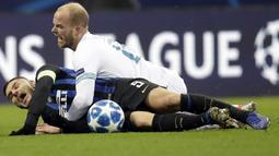 Striker Inter Milan, Mauro Icardi, terjatuh saat berebut bola dengan pemain PSV Eindhoven, Jorrit Hendrix, pada laga Liga Champions di Stadion San Siro, Italia, Selasa (11/12). Kedua tim bermain imbang 1-1. (AP/Luca Bruno)