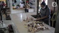 Pedagang daging ayam mengenakan masker saat berjualan di Pasar Kebayoran Lama, Jakarta Selatan, Senin (22/6/2020). Pasar Kebayoran Lama menerapkan protokol kesehatan bagi pengunjung dan pedagang untuk mengantisipasi penularan COVID-19. (Liputan6.com/Faizal Fanani)