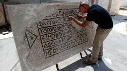 Seorang arkeolog meneliti lantai mosaik berusia 1.500 tahun di Museum Rockefeller, Yerusalem, Rabu (23/8). Penemuan langka tersebut merupakan sebuah peninggalan kuno sekaligus penemuan dokumen bersejarah sekaligus. (AHMAD GHARABLI/AFP)