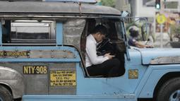 Pengemudi mobil Jeepney bermain handphone saat berada di Manila, Filipina, Jumat (22/11). Jeepney merupakan transportasi umum paling populer dan sudah menjadi ikon di Filipina. (Bola.com/M Iqbal Ichsan)