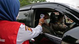 Petugas mengecek suhu tubuh saat di rest area KM 62 tol Jakarta Cikampek, Jawa Barat, Kamis (28/5/2020). Larangan mudik Idul Fitri 1441 H dan ketatnya keluar masuk kendaraan di sejumlah daerah berimbas pada penurunan pendapatan para penjual di rest area tersebut. (Liputan6.com/Herman Zakharia)