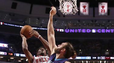 Pemain Chicago Bulls, Jimmy Butler (kiri) mencoba melakukan tembakan saat dihadang pemain Charlotte Hornets, Spencer Hawes pada laga NBA preseason basketball game di Chicago, Selasa (18/10/2016) WIB.  (AP/Charles Rex Arbogast)