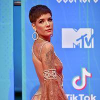 Mantan kekasih G-Eazy ini menggunakan  dress bewarna krem pada acara MTV Awards pada tahun 2018. Meskipun potongan rambutntya pendek, Halsey tetap terlihat anggun dengan tambahan aksesoris antingnya. (Kapanlagi/AFP)
