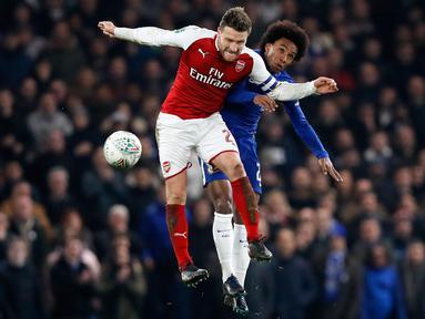 Pemain Arsenal, Shkodran Mustafi dan pemain Chelsea, Willian melompat untuk berebut bola pada laga semifinal pertama Piala Liga Inggris di Stadion Stamford Bridge, Rabu (10/1). Chelsea dan Arsenal bermain imbang tanpa gol. (AP/Kirsty Wigglesworth)