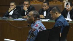 Mantan Kadis PU Papua, Mikael Kambuaya (kiri) dan Komisaris PT MBM, David Manibui saat sidang dakwaan di Pengadilan Tipikor Jakarta, Rabu (20/11/2019). Keduanya didakwa merugikan negara sekitar Rp40,93 miliar dalam pekerjaan peningkatan jalan Kemiri-Depapre TA 2015. (Liputan6.com/Helmi Fithriansyah)