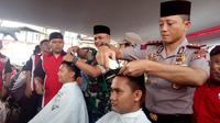 Nampak Kapolres Budi terlihat lihat memotong salah satu rambut salah satu anggota polres Garut, dalam penggalangan dana korban tsunami Selat Sunda siang tadi (Liputan6.com/Jayadi Supriadin)