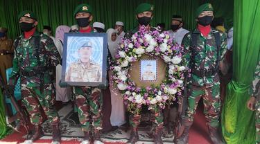 Prajurit TNI memegang foto dan karangan bunga di depan peti jenazah Pelda Anumerta Rama Wahyudi.