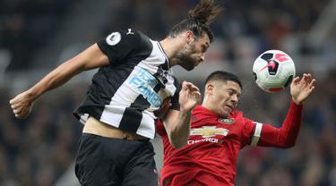 Penyerang Newcastle United, Andy Carroll berebut bola dengan pemain Manchester United, Marcos Rojo pada laga pekan kedelapan Premier League, di St James' Park, Minggu (6/10/2019). Manchester United (MU) menelan kekalahan 0-1 dari Newcastle United. (Owen Humphreys/PA via AP)