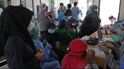 Sejumlah guru menunggu untuk vaksin COVID-19 di Puskesmas Jatiasih, Bekasi, Jawa Barat, Jumat (9/4/2021). Kementerian Pendidikan dan Kebudayaan menargetkan sebanyak 5,5 juta guru dan tenaga pendidik mengikuti vaksinasi COVID-19 sampai akhir Juni 2021. (Liputan6.com/Herman Zakharia)