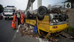 Petugas mengecek truk yang terbalik akibat salah satu ban belakang lepas di jalan tol Pondok Indah dekat pintu keluar Lebak Bulus, Jakarta, Jumat (29/5/2020). Dalam kecelakaan tersebut tidak ada korban jiwa namun membuat kendaraan yang melintas jalan tol tersendat. (merdeka.com/Dwi Narwoko)