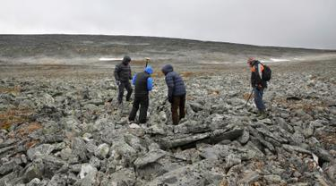 Arkelolog dan dua pemburu yang menemukan sebilah pedang milik bangsa Viking menelusuri sebuah gunung di Norwegia, 4 September 2017. Pedang dari bangsa Viking itu ditemukan pemburu rusa kutub, Einar Ambakk, saat berburu di antara bebatuan. (AP Photo)