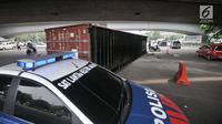 Mobil Polisi berada di dekat lokasi tergulingnya truk kontainer di kolong flyover Tomang, Jakarta, Kamis (28/6). Truk kontainer bernomor polisi BN 4706 BP tersebut terguling saat hendak berbelok arah ke Jalan Tomang Raya. (Merdeka.com/Iqbal S. Nugroho)