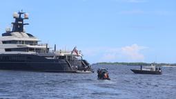 Polisi setempat mendekati kapal pesiar mewah (yacht) bernama Equanimity di Teluk Benoa, Bali, Rabu (28/2). Kapal Pesiar dengan panjang 100 meter dan berisi 34 orang kru ini memasuki perairan Bali mulai dari bulan November 2017. (Rully Prasetyo/AFP)