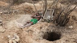 Seorang penambang beristirahat di sebelah lubang tambang safir di Sakaraha, Madagaskar. Pulau yang terletak di Samudra Hindia itu sudah menjadi salah satu produsen tambang batu mulia safir terbesar di dunia. (AFP Photo/Gianluigi Guercia)
