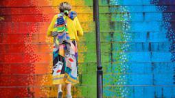 Seorang wanita berjalan menaiki tangga yang dicat dengan warna pelangi di Bucharest, Rumania, Sabtu (11/7/2020). Rumania melaporkan 698 infeksi COVID-19 baru dalam 24 jam terakhir, tingkat tertinggi sejak pandemi mencapai negara itu pada bulan Februari. (AP Photo/Vadim Ghirda)