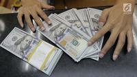 Teller menghitung mata uang dolar di penukaran uang di Jakarta, Jumat (20/4). Nilai tukar rupiah terhadap dolar Amerika Serikat (AS) mengalami pelemahan. (Liputan6.com/Angga Yuniar)