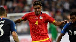 Bek Andorra, Marc Rebes (tengah) menggiring bola dari kewalan dua pemain Prancis,  Thomas Lemar dan Lucas Digne pada pertandingan grup H Kualifikasi Euro 2020 di Stade de France di Saint Denis, Paris (10/9/2019). Prancis menang telak 3-0 atas Andorra. (AFP Photo/Lionel Bonaventure)