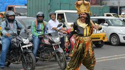 """Seniman berpakaian seperti """"Yamaraj"""" (R), dewa kematian Hindu mengatur lalu lintas di Bangalore (10/7). Kampanye ini bertujuan untuk membawa kesadaran pengendara tentang pentingnya peraturan keselamatan lalu lintas. (AFP Photo/Manjunath Kiran)"""