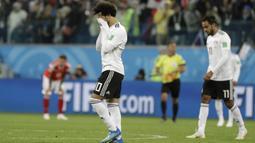 Striker Mesir, Mohamed Salah, menutup wajahnya usai ditaklukkan Rusia pada laga Piala Dunia 2018 di Stadion Krestovsky, Saint-Petersburg, Rabu (20/6/2018). Rusia menang 3-1 atas Mesir. (AP/Gregorio Borgia)