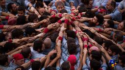 Para Castellers membentuk fondasi untuk menara manusia atau 'Castell' di alun-alun Sant Jaume, Barcelona, Spanyol, Minggu (24/9). Ribuan orang separatis Catalonia mendukung referendum kemerdekaan bagian timur Spanyol tersebut. (AP Photo/Emilio Morenatti)