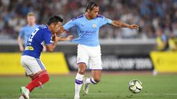 Gelandang Yokohama Marinos, Takuya Kida, berebut bola dengan gelandang Manchester City, Leroy Sane, pada laga pramusim di Stadion Yokohama, Jepang, Sabtu (27/7). Yokohama kalah 1-3 dari City. (AFP/Charly Triballeau)